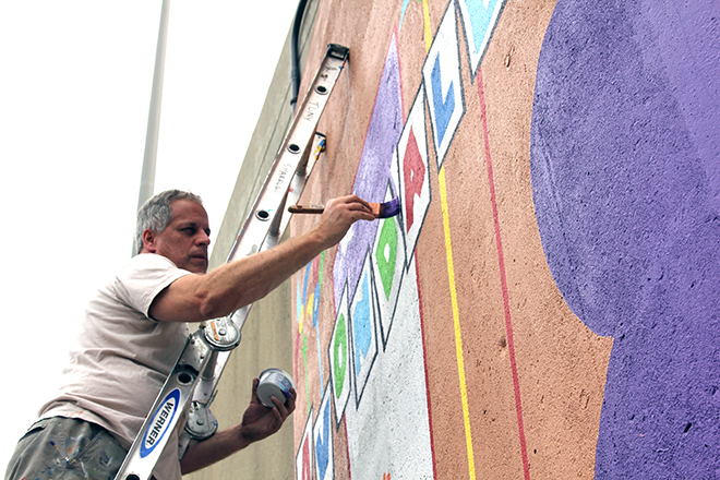 Tony Passero Whoot Owl Mural on Belmont and Kedzie in Chicago, IL Day 14 Artist Tony Passero Adding in the purple in the Avondale Marker
