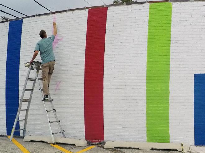 Tony Passero JagLeo Mural Day 1 artist Tony Passero trimming a color