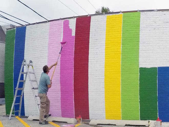 Tony Passero JagLeo Mural Day 1 artist Tony Passero rolling out a color column